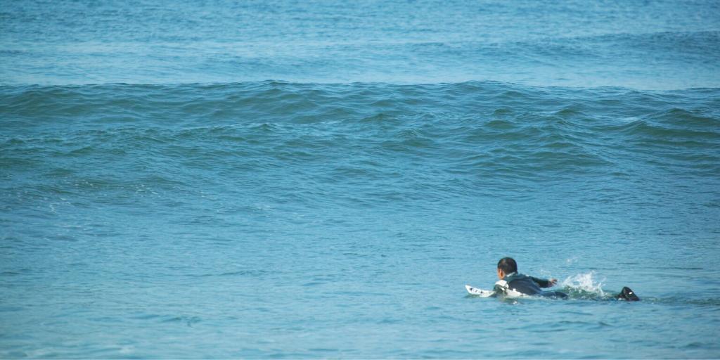 Welle anpaddeln beim Surfen